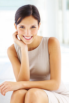 Buy stock photo Portrait of pretty young businesswoman sitting with hand on chin and smiling