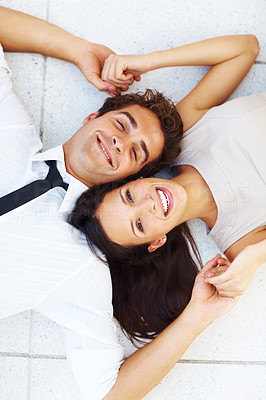 Buy stock photo Closeup of beautiful young business couple lying on floor holding hands and smiling