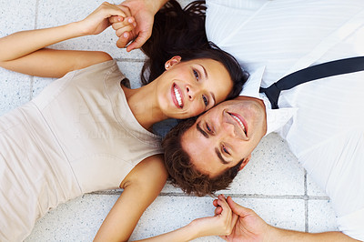 Buy stock photo Top view of happy young couple lying down on floor smiling