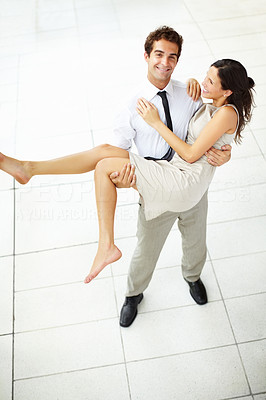 Buy stock photo Top view of smart young man romantically carrying cute girlfriend in his arms