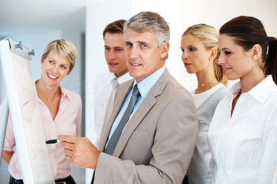 Buy stock photo Confident male leader explaining on white board to his team