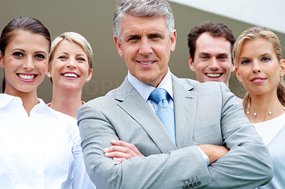 Buy stock photo Portrait of confident mature businessman smiling with his staff in background
