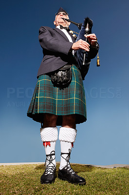 Buy stock photo Low angle view of a senior highlander wearing kilt and playing bagpipes