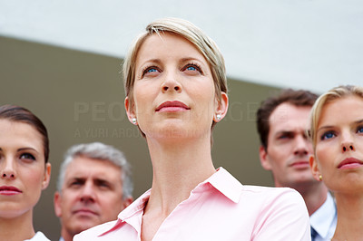 Buy stock photo Ambitious young female business executive looking away with her coworkers in background