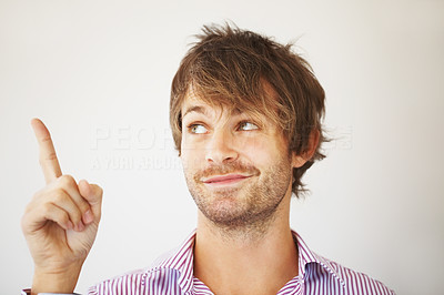 Buy stock photo Closeup of handsome young man pointing up on white background