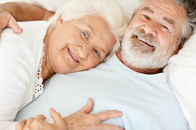 Buy stock photo Portrait of a loving senior couple lying in bed