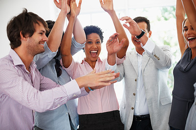 Buy stock photo Business team enjoying success with their hands raised