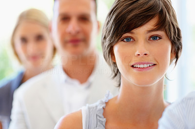 Buy stock photo Focus on smiling woman with group in row behind her