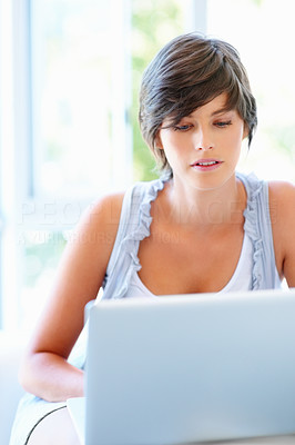 Buy stock photo View of woman concentrating while working on laptop