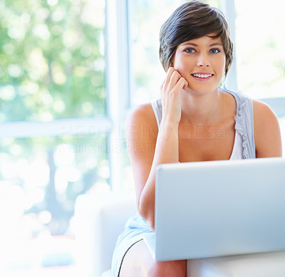 Buy stock photo Pretty young woman smiling at the camera, at home in her brightly lit lounge with her laptop on her lap - copyspace