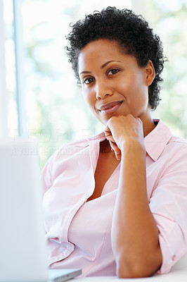 Buy stock photo Pretty woman resting her chin on her hand while in front of laptop