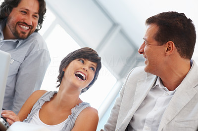 Buy stock photo Cheerful business woman having friendly chat with colleagues at office