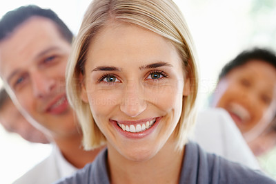 Buy stock photo Closeup of smiling young business woman with blur team in background