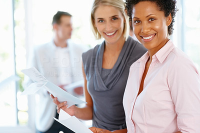 Buy stock photo Successful business women holding documents with man in background