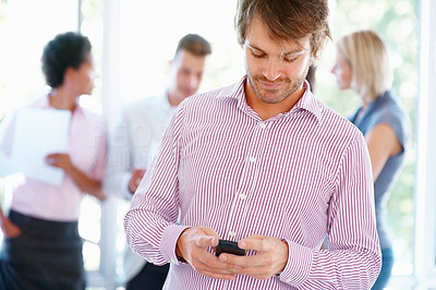Buy stock photo Young man sending text message with people in background
