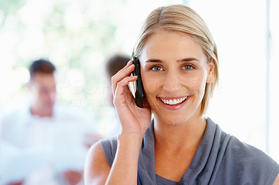 Buy stock photo Happy woman talking on cell phone with team in background