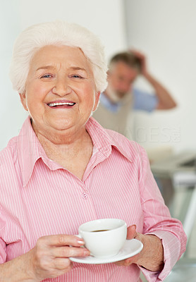 Buy stock photo Portrait of a happy elderly woman drinking coffee with her husband in the background