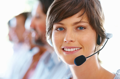 Buy stock photo Smiling call center executive with colleagues in blur background