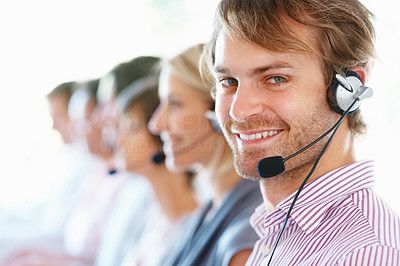 Buy stock photo Closeup of smiling call center executive with his team in blur background