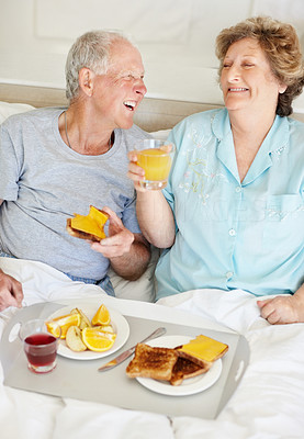 Buy stock photo A senior couple laughing while having breakfast in bed