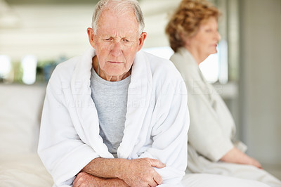 Buy stock photo Shot of an elderly couple sitting on their bed after an argument