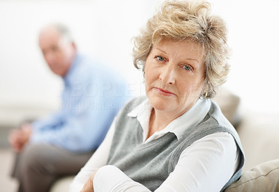 Buy stock photo Portrait of a senior woman sitting on the opposite end of a sofa from her husband after an argument