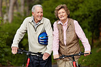 Happy matured couple walking with bicycle in countryside