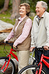 Sporty mature couple walking with bicycle in countryside