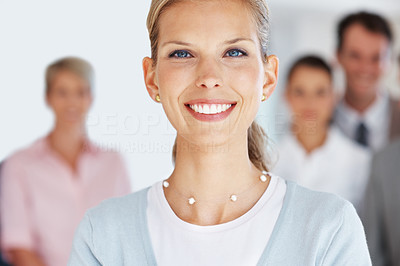 Buy stock photo Portrait of an attractive young businesswoman standing in front of her team