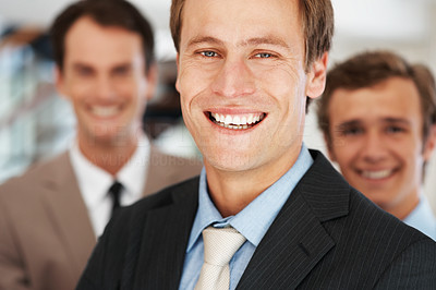 Buy stock photo Closeup portrait of a handsome young businessman smiling with team in background