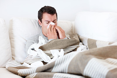 Young man blowing his nose while in bed from his allergies