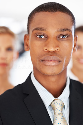 Buy stock photo Young african american businessman standing with his colleagues in background