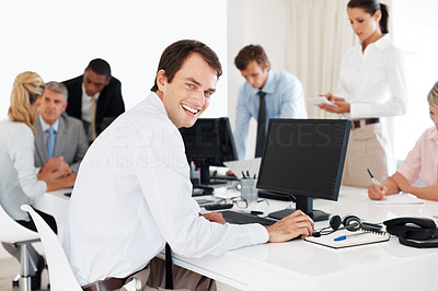 Buy stock photo Portrait of a confident young businessman working on computer with his colleagues at office