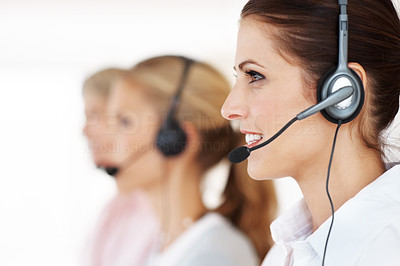 Buy stock photo Beautiful female helpdesk operator answering call with her colleagues in the background