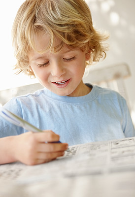 Buy stock photo Portrait of a happy boy with pen writing something on newspaper