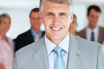 Buy stock photo Portrait of a smart mature business manager smiling and his team standing in background