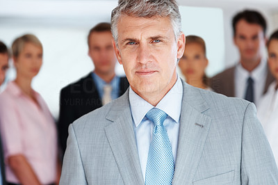 Buy stock photo Portrait of a confident mature businessman standing in front of his team