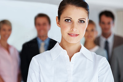 Buy stock photo Portrait of a confident young businesswoman standing with her colleagues in background