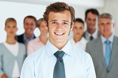 Buy stock photo Portrait of a smart young businessman smiling and his colleagues standing at the back