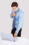 Businessman wearing tie and getting ready while using laptop