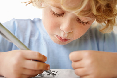 Buy stock photo Closeup portrait of an adorable boy holding a pen while solving a crossword puzzle