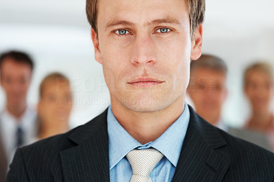 Buy stock photo Portrait of a confident young businessman and his colleagues standing in background