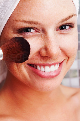Closeup of a happy woman applying make up to face after a bath