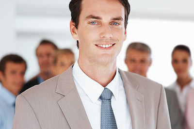 Buy stock photo Portrait of a smart young businessman smiling and his colleagues at the back
