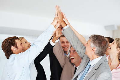 Buy stock photo Happy group of businesspeople giving high five to each other and enjoying their success