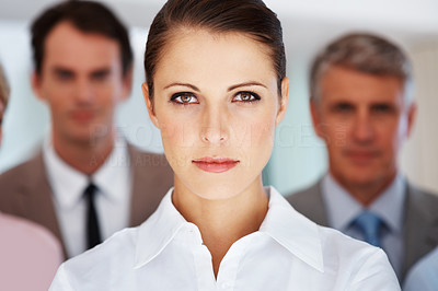 Buy stock photo Portrait of a confident young business woman and her team standing in background