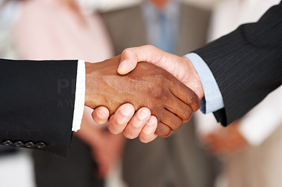 Buy stock photo Closeup of a business man greeting eachother with colleagues blurred in background