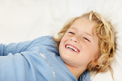 Buy stock photo Closeup portrait of cheerful innocent boy lying on bed