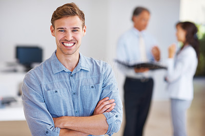 Young business man standing with arms crossed