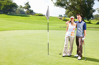 Golfing couple standing on the putting green